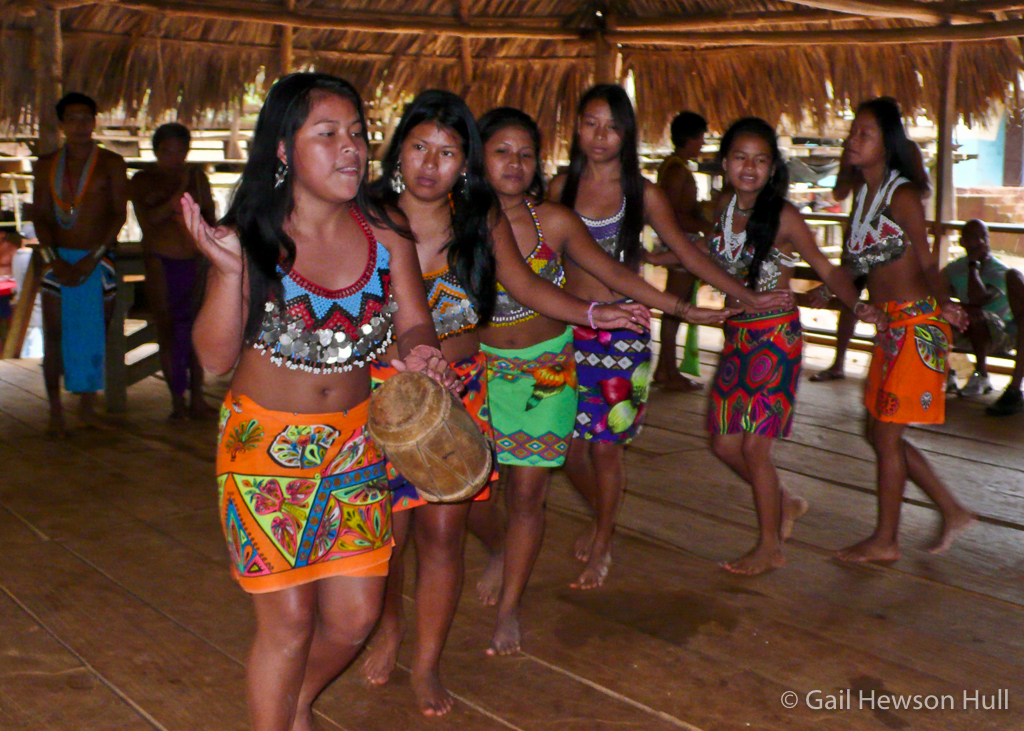 Adolescent girls dance demurely for paying guests.