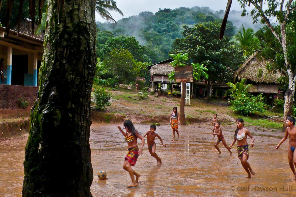 Children play soccer in the rain.