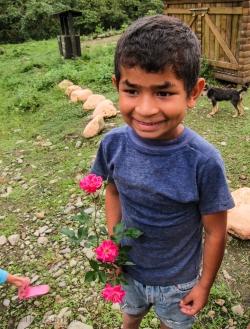 Boy with distinct eyebrows, clutching roses, Mashpi, Ecuador, 2014